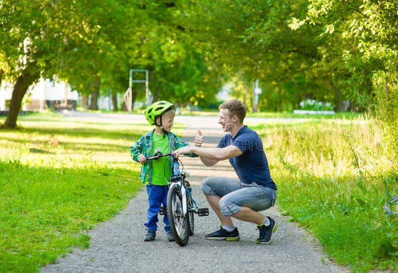 生谈话与他的骑自行车的儿子 免版税库存照片