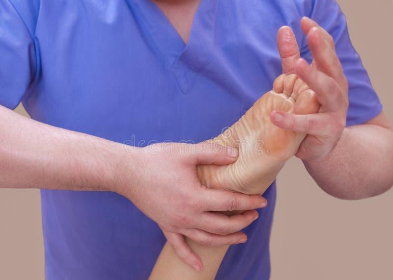 医生足病医生做耐心` s脚的考试和按摩 免版税库存照片