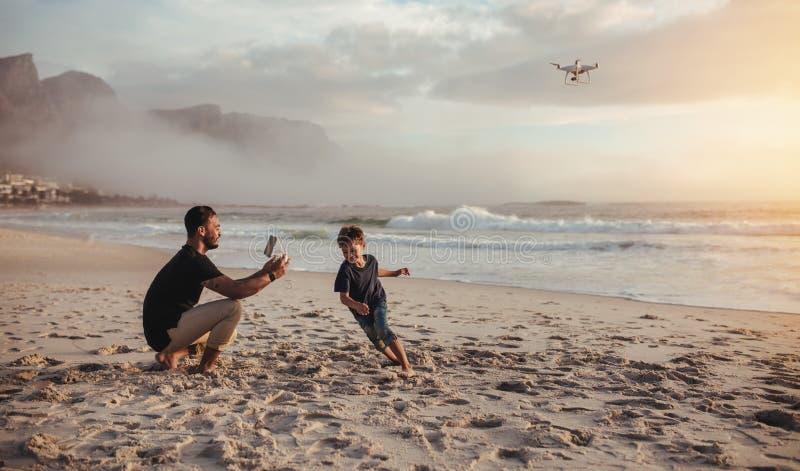 生跑在海滩的飞行寄生虫和儿子 库存照片