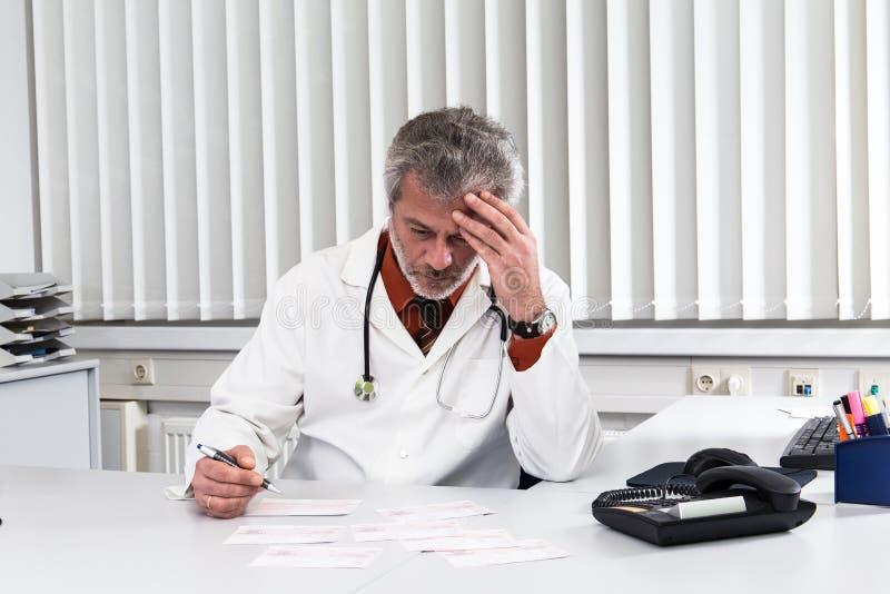 医生过度紧张在他的办公桌 库存照片