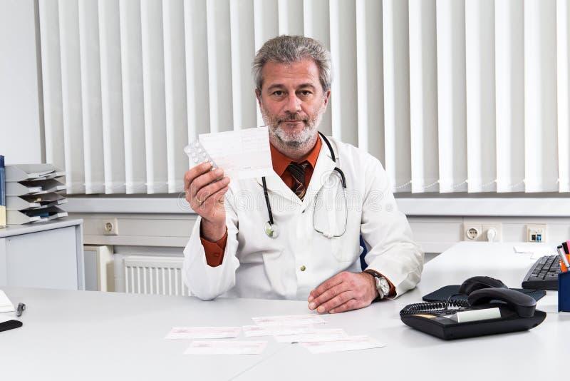 医生过度紧张在他的办公桌 免版税库存图片