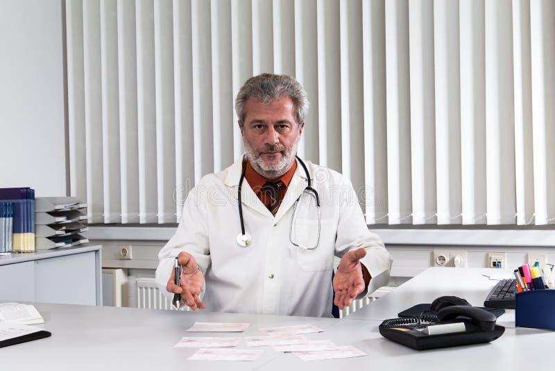 医生过度紧张在他的办公桌 免版税库存照片