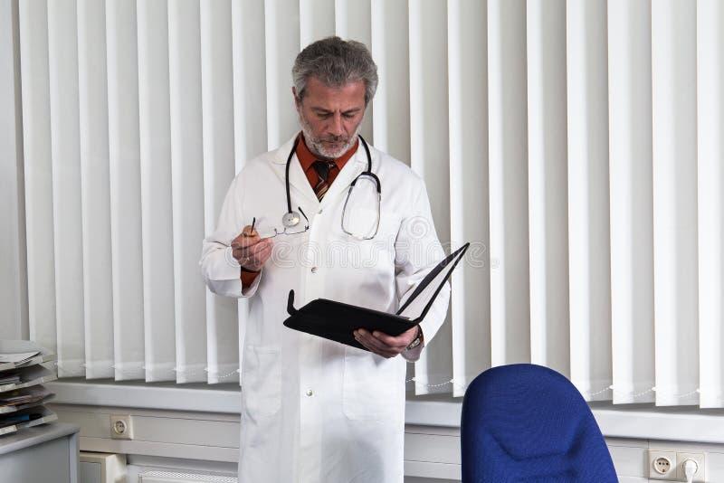 医生过度紧张在他的办公桌 图库摄影