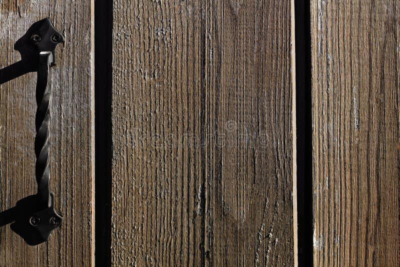 生铁在一个木门的门把手 黑褐色木背景 老破旧的委员会 被抓的木墙壁 库存图片