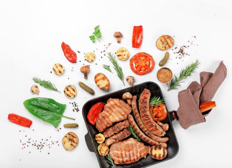 生铁格栅平底锅用牛排,香肠,烤了菜 免版税图库摄影