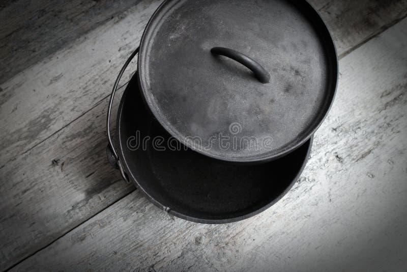 生铁荷兰烘箱一半开放在木背景 免版税库存图片