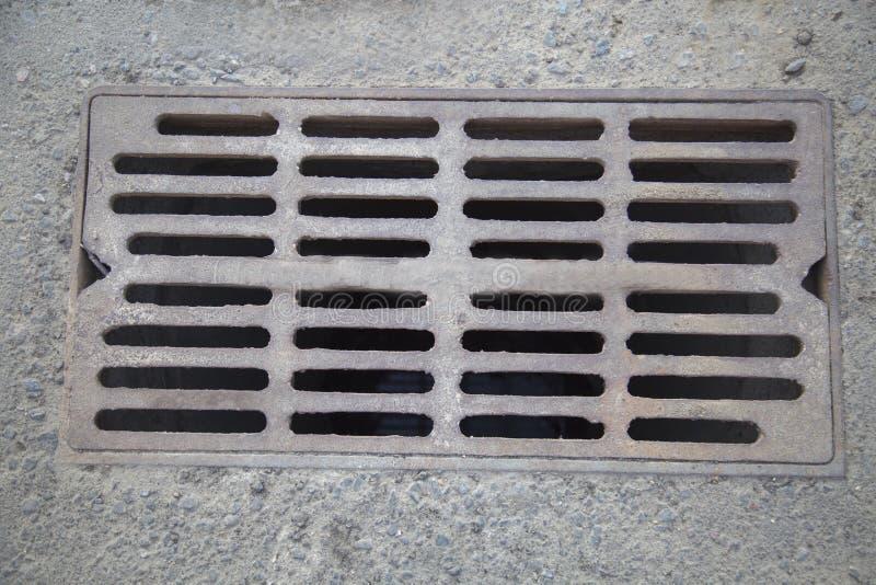 生铁风暴花格被修造入沥青 免版税库存照片