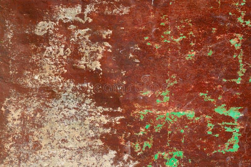 生锈和脏的金属铁板材墙壁有典型的氧化铁红颜色的和有绿色削皮涂层纹理背景 图库摄影