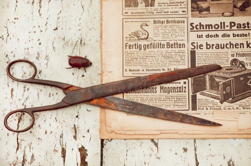 生锈的剪刀和爬行的甲虫在背景与老报纸-葡萄酒刻记了例证- 免版税库存照片