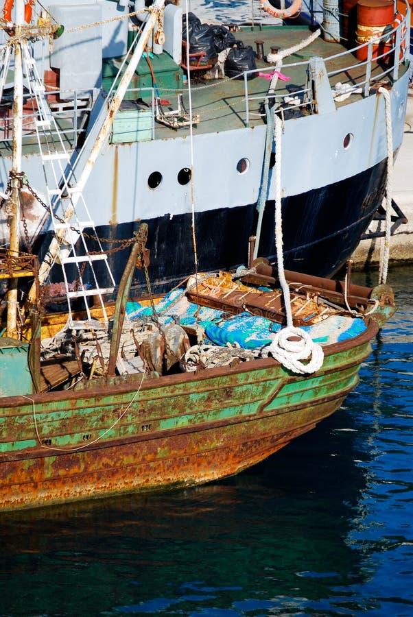 生锈的商业船和现代集装箱船在口岸 免版税图库摄影