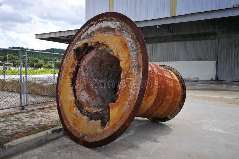 生锈的大机器零件,安置户外在工厂区域 免版税库存照片