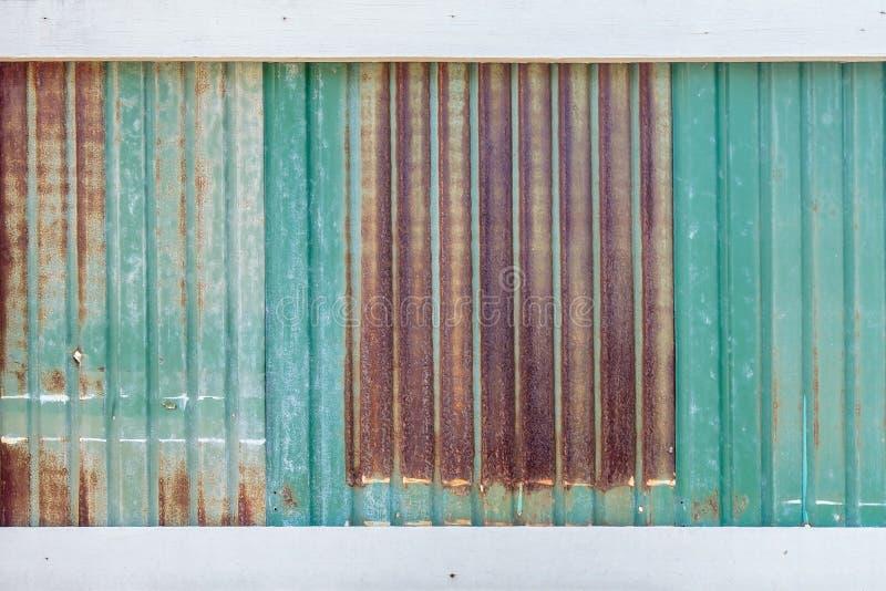 生锈的波纹状的金属墙壁或生锈的锌难看的东西和白色木板条 图库摄影