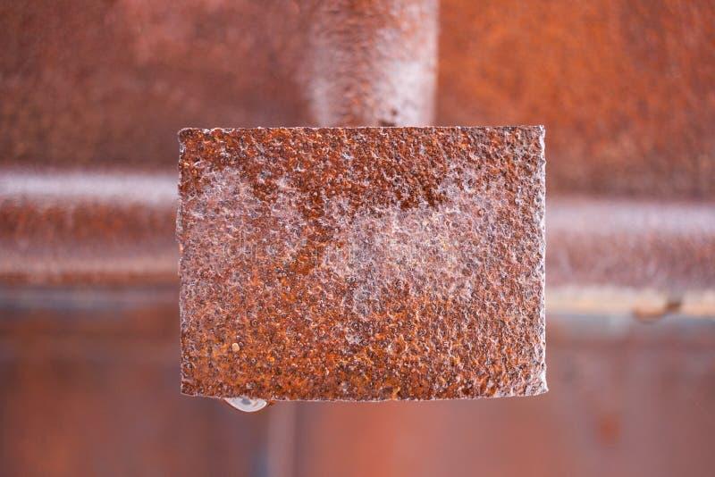 生锈的湿金属长方形板材在框架中部  免版税库存图片