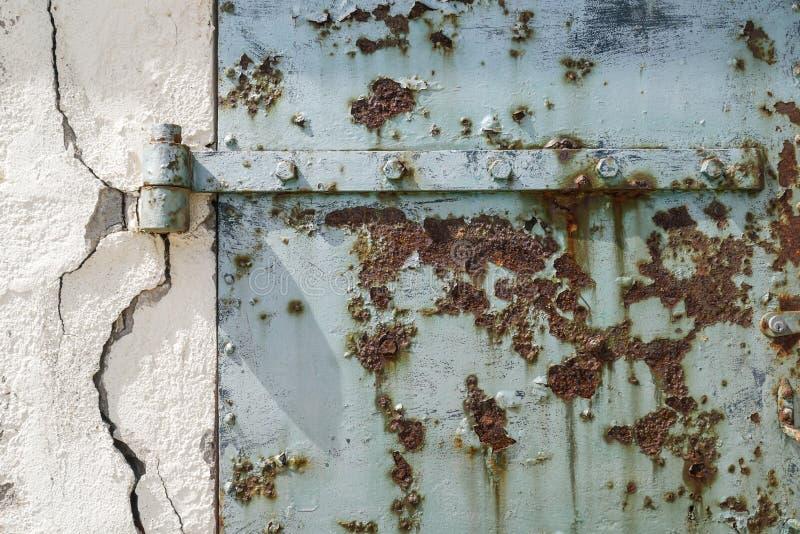 生锈的老蓝色门有破裂的墙壁,抽象和织地不很细背景 免版税库存图片