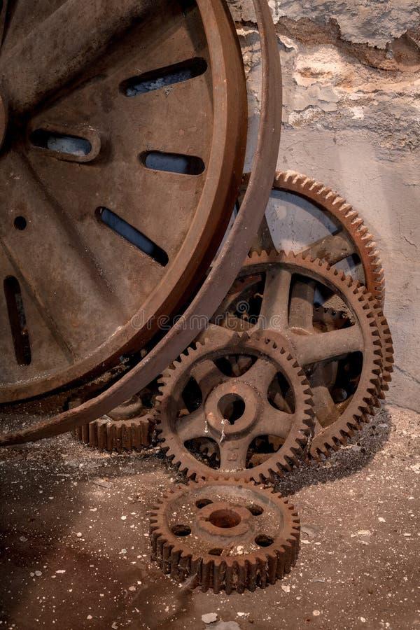 生锈的老齿轮放置对水泥墙壁 免版税库存照片