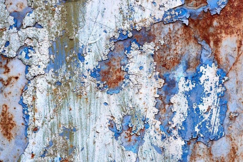 生锈的蓝色和白色被绘的墙壁 背景被腐蚀的金属 免版税库存图片
