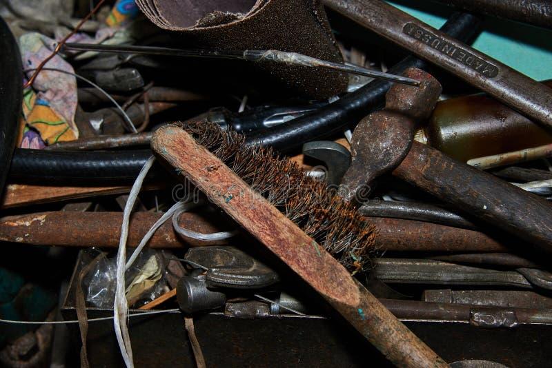 生锈的金属刷子和锤子在工作凳有在苏联制造的生锈的板钳的在背景 库存图片