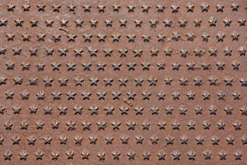 生锈的铁熔铸了用五针对性的特征模式盖的盘区 免版税图库摄影