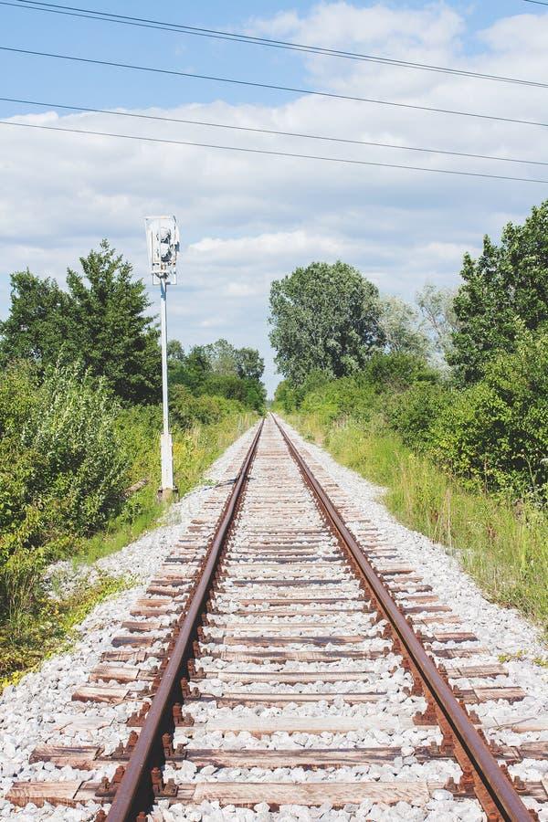 生锈的铁轨和睡眠者在白色石渣,围拢与绿叶和蓝天 免版税图库摄影