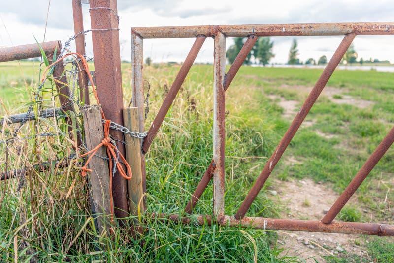 生锈的铁门关闭了与一条被打结的橙色绳索和钢ch 免版税库存图片