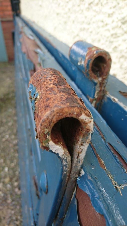 生锈的铰链蓝色门削皮油漆门 库存照片