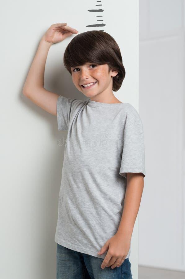 生长高和测量的男孩 免版税库存图片