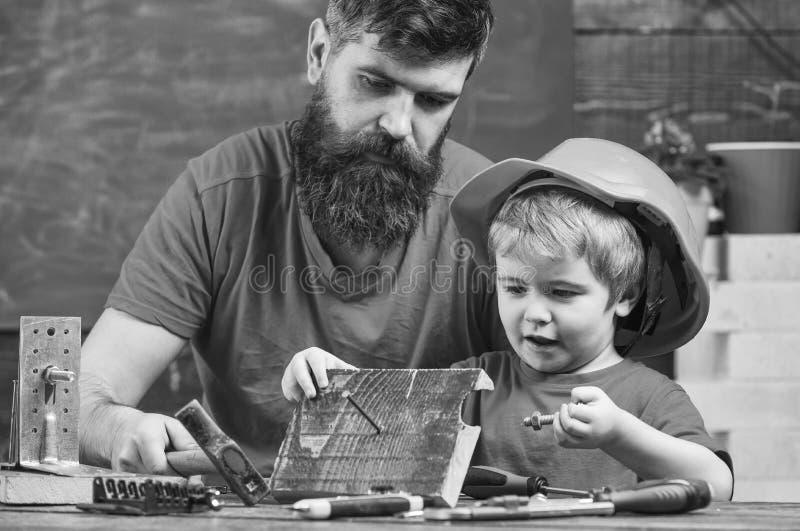 生,做父母与教小儿子的胡子使用短钉和锤子 男性责任概念 男孩,繁忙的孩子  库存照片