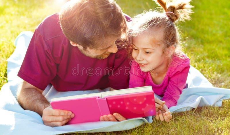 生读书给他的女儿在庭院里 库存图片