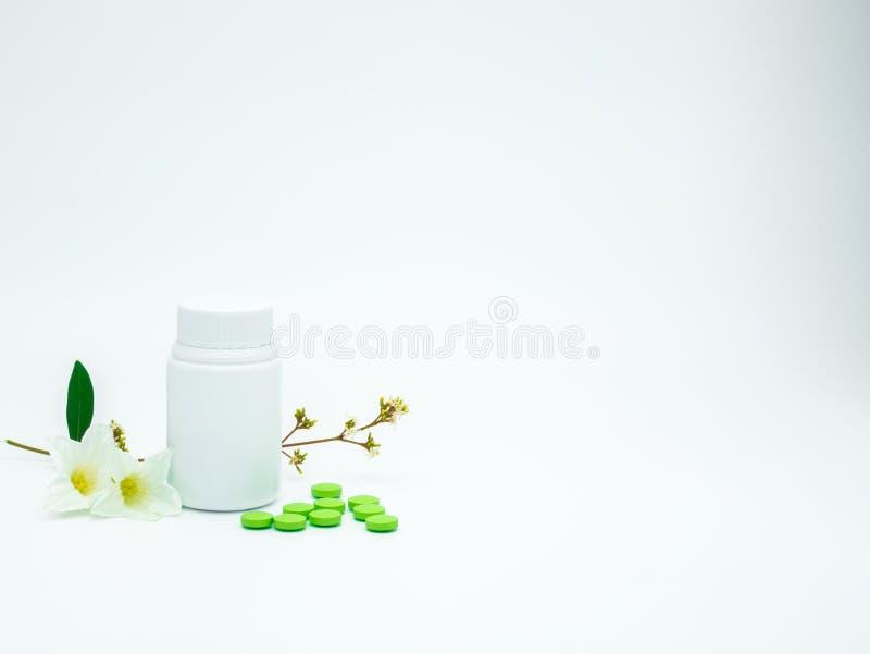 维生素和补充压片与花和分支的药片并且删去在白色背景的标签塑料瓶与拷贝空间 免版税库存照片