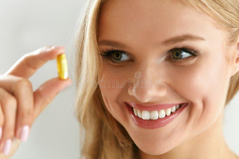 维生素和补充 拿着鱼油胶囊的美丽的妇女 图库摄影