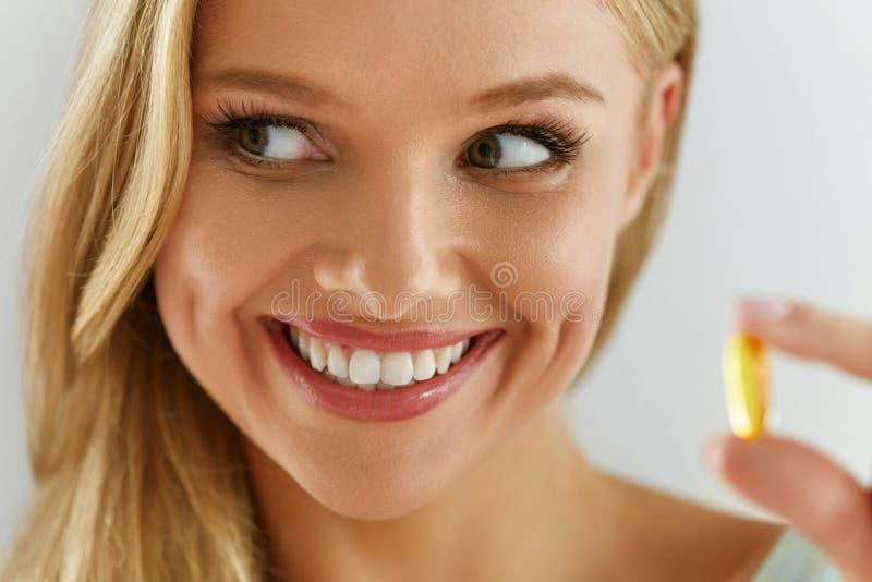 维生素和补充 拿着鱼油胶囊的美丽的妇女 免版税图库摄影