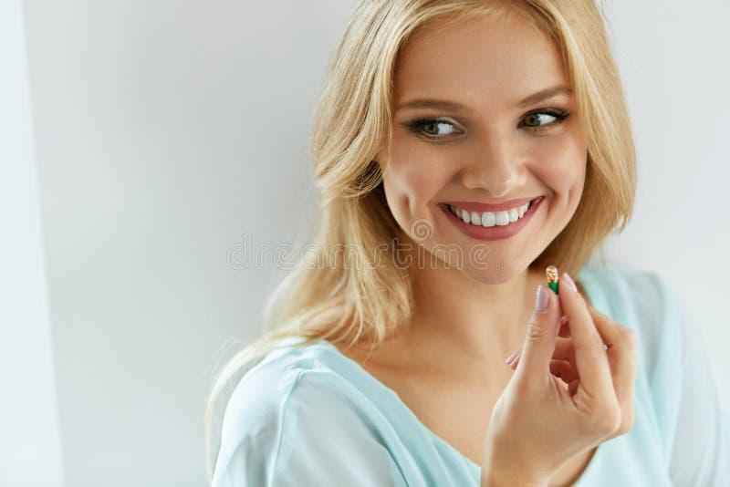 维生素和食物补充 有药片的美丽的妇女在手中 库存照片