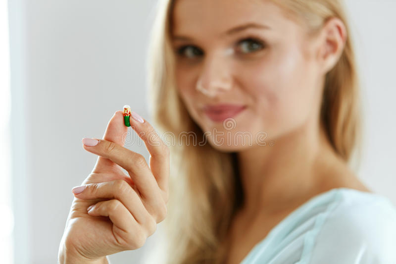维生素和食物补充 有药片的美丽的妇女在手中 库存图片
