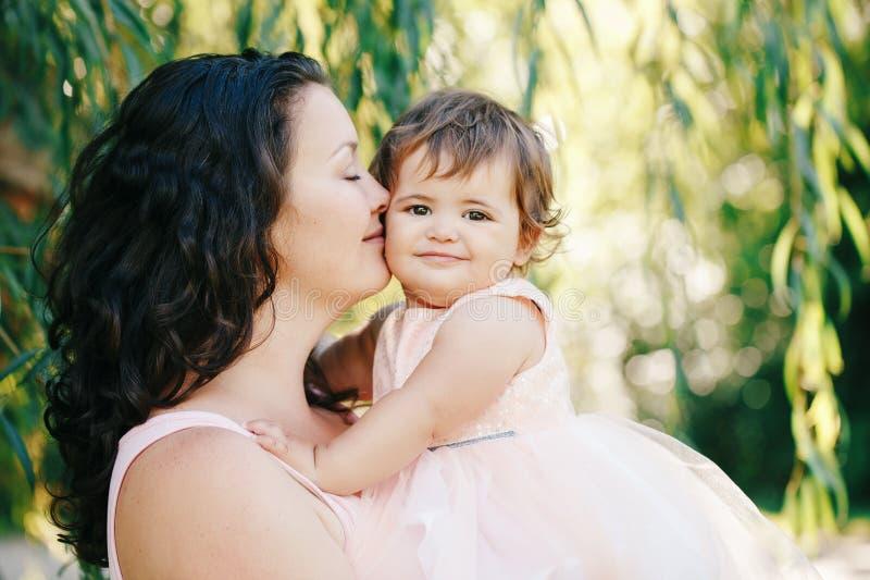 生活方式举行拥抱的美丽的白白种人深色的母亲小组画象桃红色礼服的女儿亲吻她的在面颊 免版税库存照片