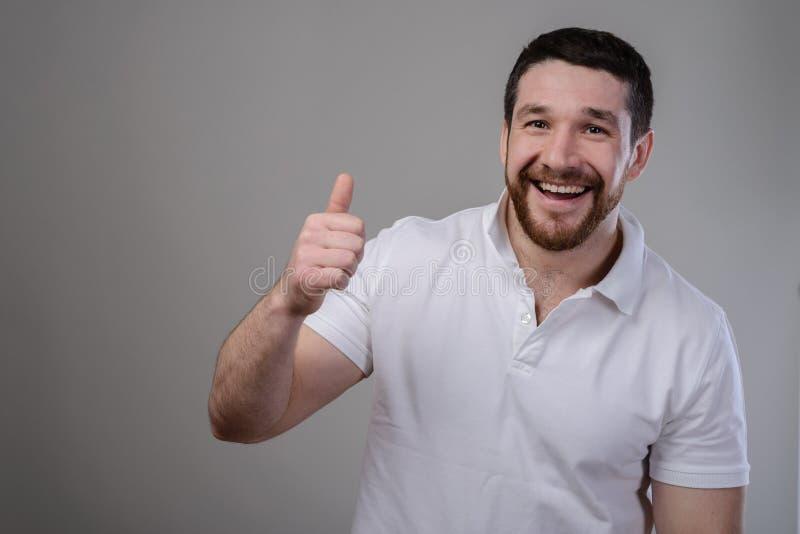生活方式和人概念:愉快的英俊的显示在被隔绝的背景的人佩带的白色T恤杉赞许 免版税图库摄影