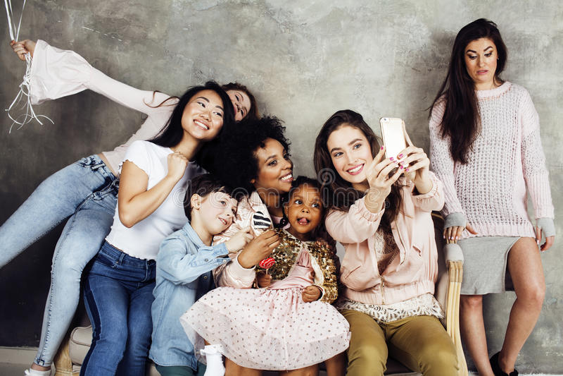 生活方式和人概念:用庆祝在诞生天的不同的年龄孩子的年轻俏丽的变化国家妇女 库存照片