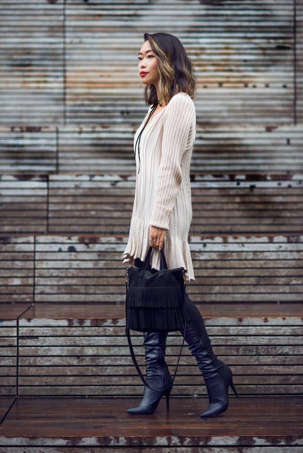 生活方式走与黑袋子佩带的秋天成套装备的美丽的亚裔妇女时尚画象  免版税库存图片