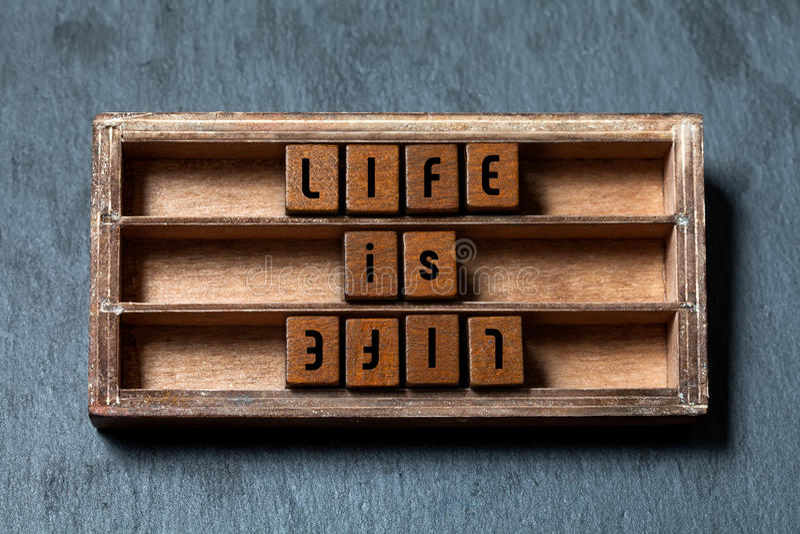 生活是生活,在对手概念对面 破旧的木箱,与老牌信件的立方体,灰色石头构造了背景 免版税库存照片