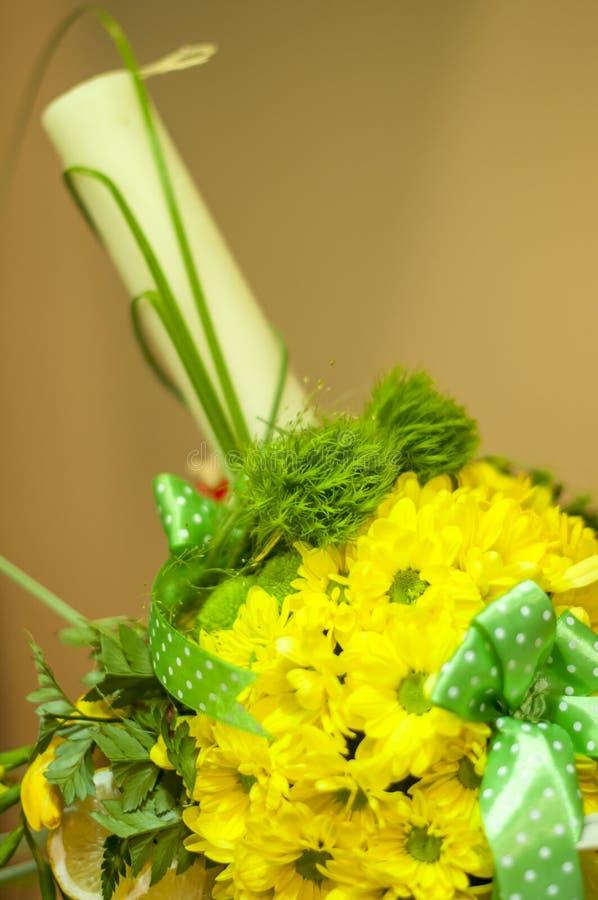 一个洗礼蜡烛的特写镜头与黄色花的 库存照片