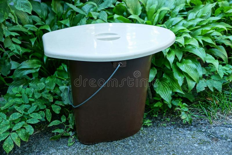 用一个灰色盒盖盖的塑料桶在路面的街道上站立在绿色植被附近 库存照片