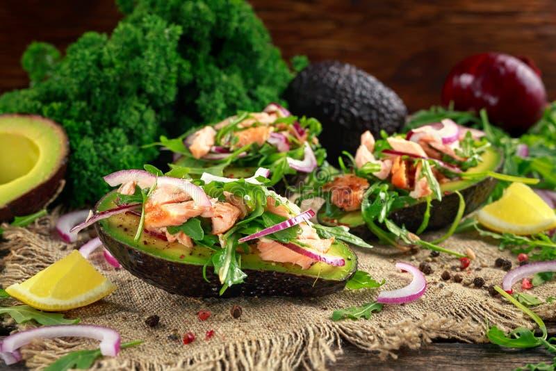 用三文鱼、红洋葱和芝麻菜充塞的鲕梨小船 概念健康食物 库存照片