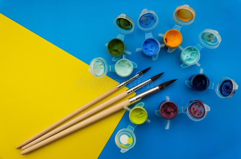 用不同的丙烯酸酯或油漆和刷子的平的被放置的构成在难看的东西背景 免版税库存照片