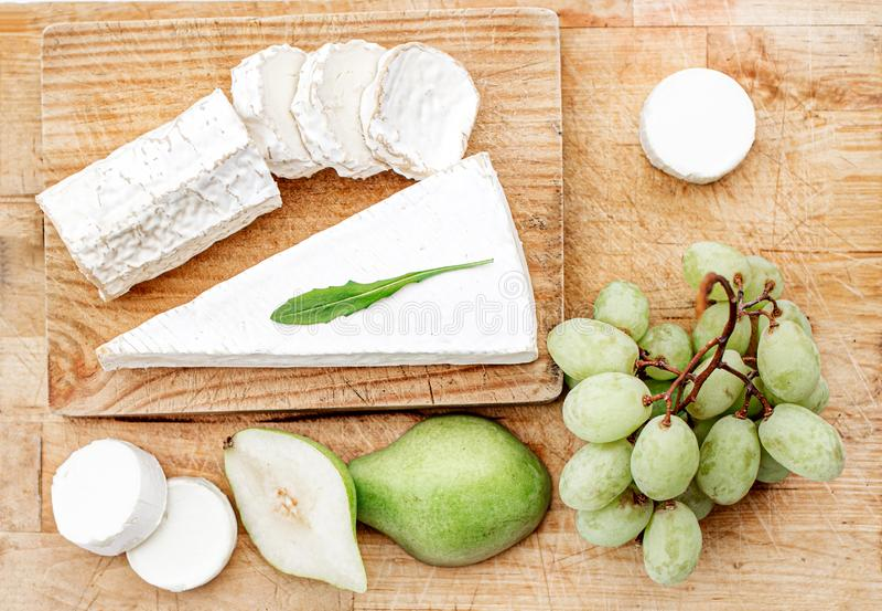 用不同的乳酪、梨和葡萄的乳酪板在白色木背景 乳酪盛肉盘顶视图 r 库存图片
