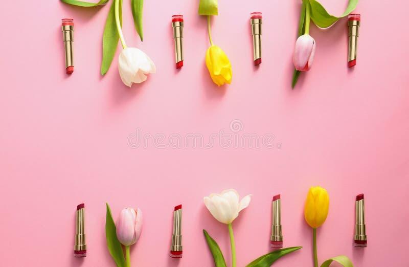 用不同的唇膏和郁金香花的平的被放置的构成在颜色背景 免版税库存图片