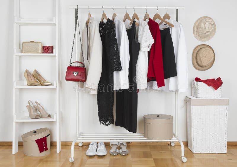 用不同的女性衣裳、帽子和鞋子的现代衣橱内部 图库摄影