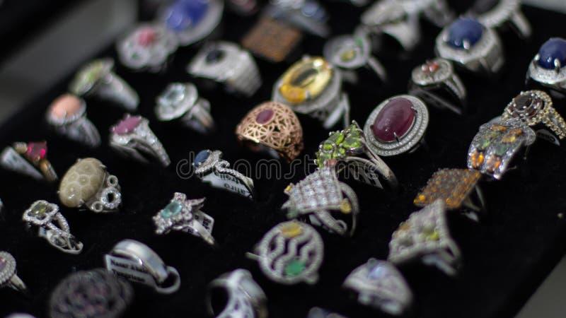 用不同的宝石、材料、大小和形状的圆环在首饰的显示 库存照片