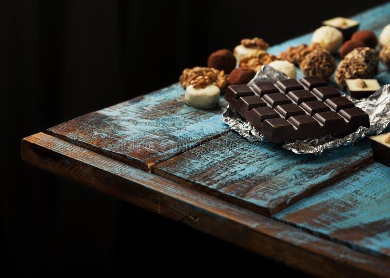 用不同的巧克力的黑暗的巧克力块在木桌上 免版税库存图片