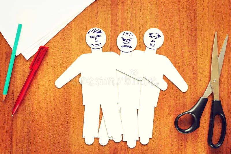 用不同的情感的三个纸男性角色 库存照片