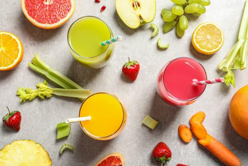 用不同的杯的平的被放置的构成汁液和新鲜的成份 库存照片