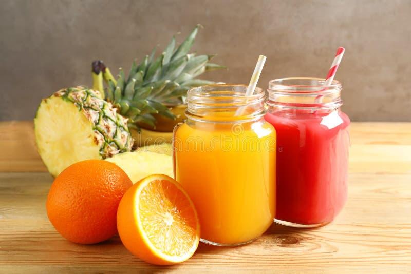 用不同的汁液和新鲜水果的金属螺盖玻璃瓶在木桌上 免版税库存图片
